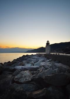 Prachtige zonsondergang over de zee in ligurië in camogli met uitzicht op de vuurtoren in de verte