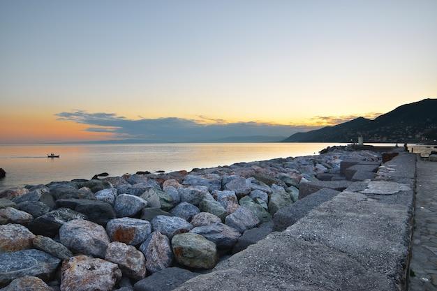 Prachtige zonsondergang over de zee met frame van kleurrijke stenen