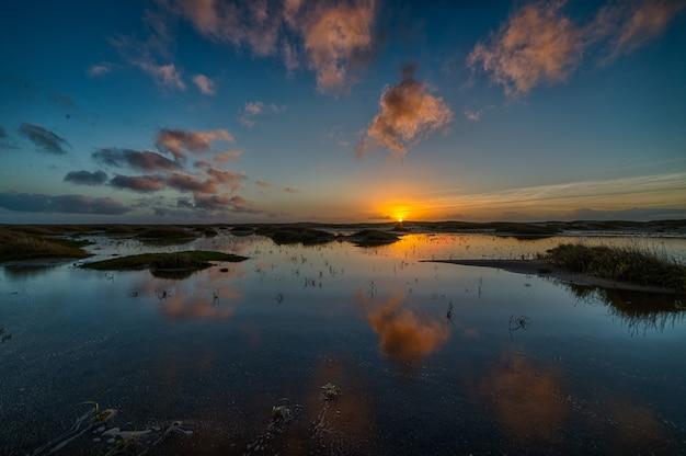 Prachtige zonsondergang weerspiegelt in de zee en creëert het perfecte landschap voor avondwandelingen