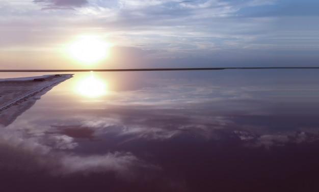 Prachtige zonsopgang boven een roze meer bij een klein eiland, de weerspiegeling van de blauwe lucht op het water, de paarse kleur van het zeegezicht.