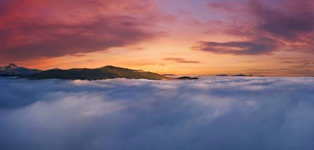 Prachtige zonsopgang hoog in de bergen boven de wolken. dramatisch natuurlijk landschap met bergen, mist en lucht.