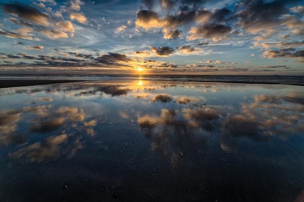Prachtige zonsopgang weerspiegelt in de zee en creëert het perfecte landschap voor ochtendwandelingen