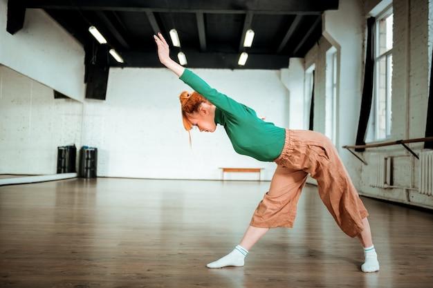 Praktijk. goed uitziende slanke yogacoach die een groene coltrui draagt en er betrokken uitziet