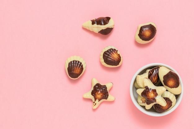 Pralines in de vorm van schelpdieren en schelpen. de zoetheid van melkchocolade. het uitzicht vanaf de top. plat leggen.
