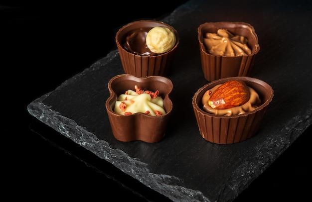 Pralines met slagroom en noten op een bord leisteen sorteren geassorteerde chocolade op geïsoleerde zwarte achtergrond