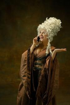 Praten aan de telefoon. portret van middeleeuwse jonge vrouw in bruine vintage kleding op donkere achtergrond. vrouwelijk model als hertogin, koninklijk persoon. concept vergelijking van tijdperken, modern, mode, schoonheid.