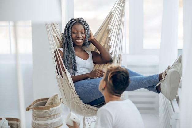Praten. donkerhuidige lachend meisje zittend in een hangende stoel en praat met haar vriendin