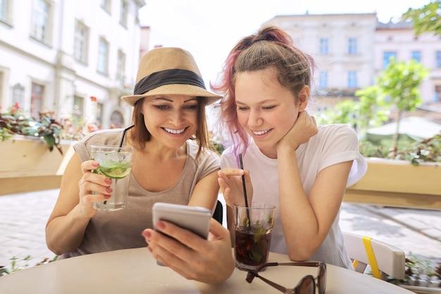 Praten en frisdrank drinken moeder dochter tiener, glimlachende vrouwen zitten in het terras, kijken naar smartphone. vriendschap en communicatie van ouder en kind van tiener