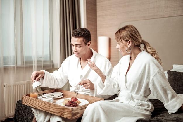 Praten met echtgenoot. blond-haired vrouw die witte badjas draagt die met echtgenoot zijn smakelijk ontbijt heeft
