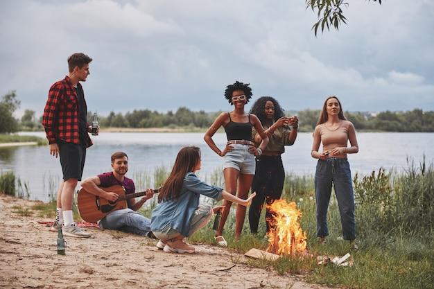 Praten met elkaar. groep mensen hebben picknick op het strand. vrienden hebben plezier in het weekend.