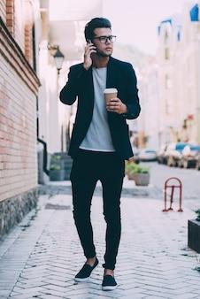 Praten met vriend. volledige lengte van knappe jongeman in slimme vrijetijdskleding met koffiekopje en pratend op mobiele telefoon terwijl hij langs de straat loopt