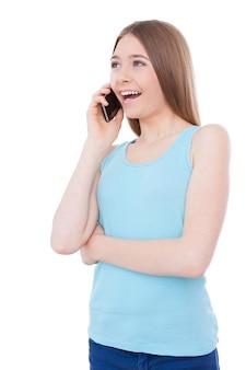 Praten met vriendje. vrolijk tienermeisje dat op de mobiele telefoon praat en glimlacht terwijl ze geïsoleerd op wit staat