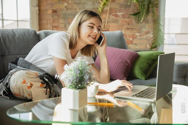 Praten over de telefoon. blanke vrouw, freelancer tijdens het werk in thuiskantoor tijdens quarantaine. jonge zakenvrouw thuis, zelf geïsoleerd. gadgets gebruiken. werken op afstand, preventie van verspreiding van coronavirus.