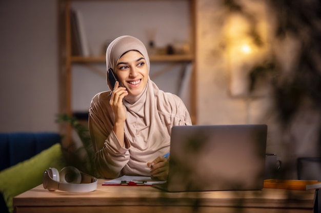 Praten over de telefoon. gelukkige moslimvrouw thuis tijdens online les. moderne technologieën, onderwijs op afstand, etniciteit en traditie concept. menselijke emoties, levensstijl. met behulp van laptop om thuis te zitten.