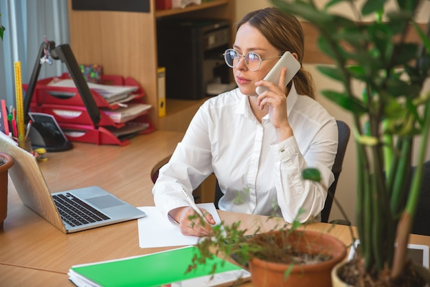 Praten over de telefoon. kaukasische ondernemer, zakenvrouw, manager die geconcentreerd op kantoor werkt. ziet er serieus en druk uit, gekleed in klassieke kleding. concept van werk, financiën, zaken, succes, leiderschap.