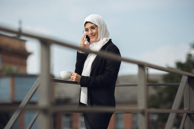 Praten over de telefoon. mooi moslim succesvol zakenvrouwportret, zelfverzekerde gelukkige ceo, leider, baas of manager. apparaten gebruiken, gadgets, onderweg werken, ziet er druk uit. charmant. inclusief, diversiteit.