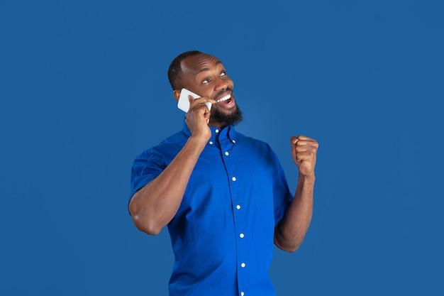 Praten over de telefoon. zwart-wit portret van jonge afro-amerikaanse man geïsoleerd op blauwe muur. mooi mannelijk model. menselijke emoties, gezichtsuitdrukking, verkoop, advertentieconcept. jeugd cultuur.