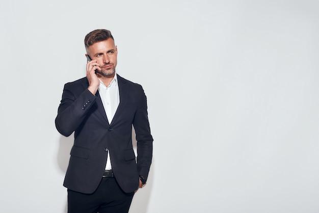 Praten over zakelijke knappe bebaarde zakenman die aan de telefoon praat terwijl hij tegen grijs staat