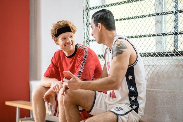 Praten. twee basketbalspelers zitten in een kleedkamer en praten