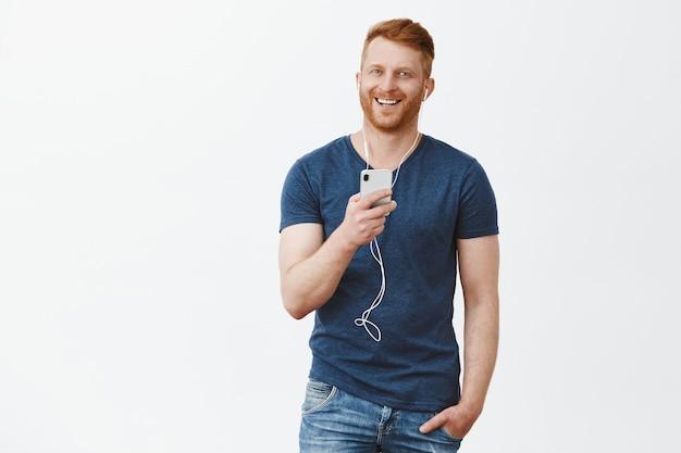 Praten via oortelefoons comfortabeler. portret van gelukkig aantrekkelijk mannelijk roodharig mannelijk model in blauw t-shirt, smarpthone vasthouden, muziek luisteren met oordopjes en breed glimlachend