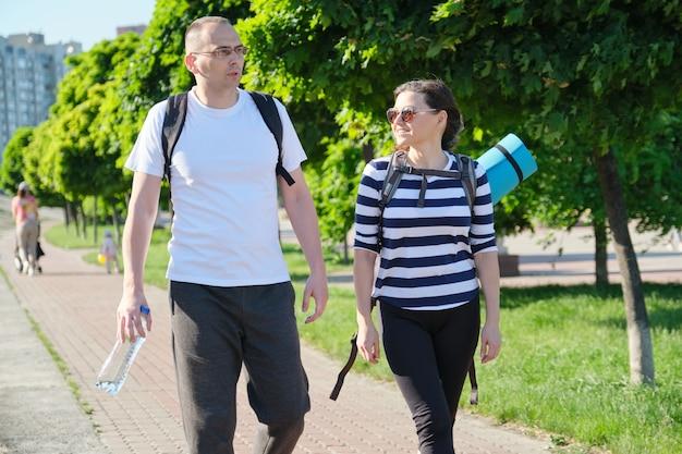 Pratende man en vrouw van middelbare leeftijd, paar dat langs parkweg d mensen loopt