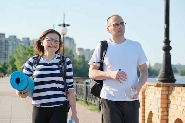 Pratende man en vrouw van middelbare leeftijd, paar wandelen langs parkweg