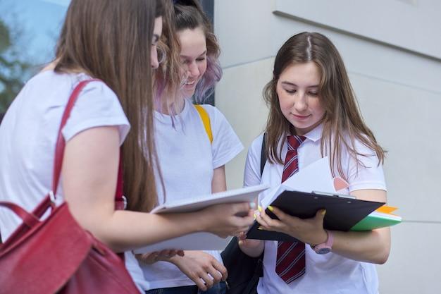 Pratende studentenmeisjes. drie tieners met rugzakken, boeken, buiten lachen en praten