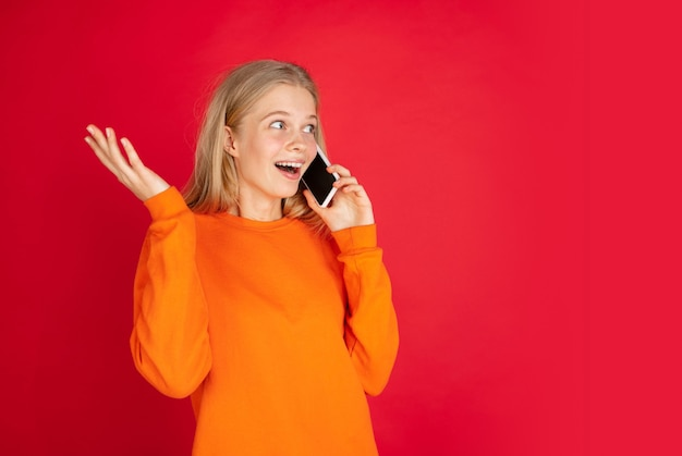 Pratende telefoon. portret van jonge blanke vrouw geïsoleerd op rode studio achtergrond met copyspace. mooi vrouwelijk model. concept van menselijke emoties, gezichtsuitdrukking, verkoop, advertentie, jeugd. folder