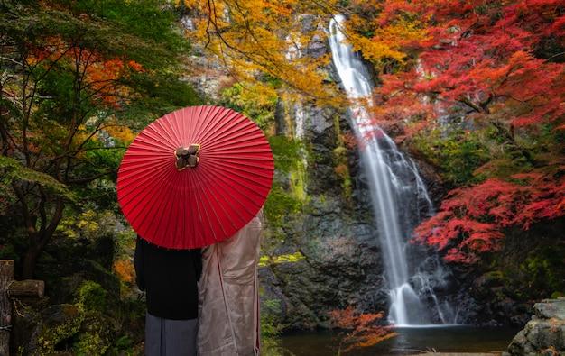 Pre-huwelijksfoto voor japans paar en rode paraplu op de rode brug in de minoh-waterval