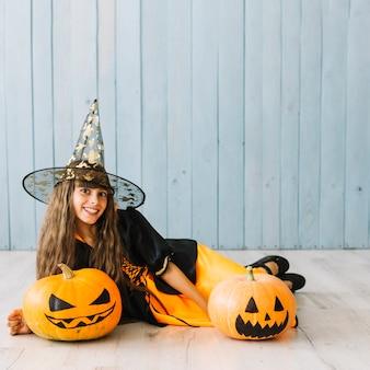 Pre-tienermeisje in heksenkostuum die op vloer met pompoenen liggen