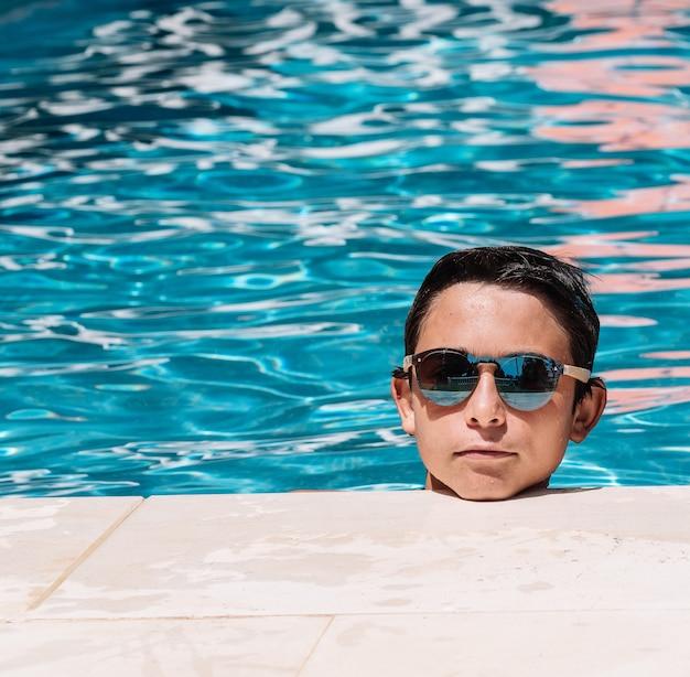 Pre-tieners poseren met een zonnebril bij de rand van het zwembad