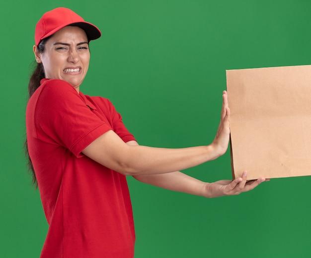 Precies jong leveringsmeisje die eenvormig en glb dragen die document voedselpakket geven aan cliënt die op groene muur wordt geïsoleerd