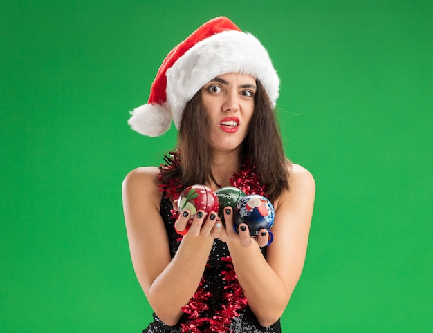 Precies jong mooi meisje dat kerstmishoed met slinger op hals draagt die de bal van de kerstmisboom uithoudt die op groene muur wordt geïsoleerd