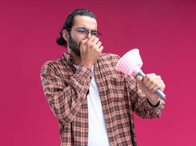 Precies jonge knappe schoonmaakster die t-shirt draagt ?? en kijkt naar de sluitende neus van de zuiger die op roze muur wordt geïsoleerd