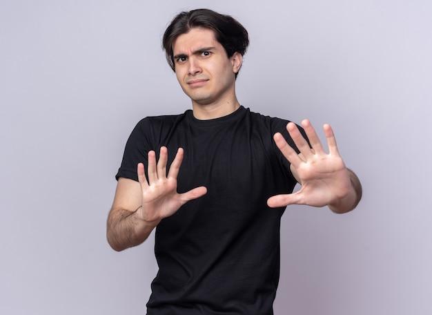 Preek jonge knappe kerel die zwarte t-shirt draagt die stopgebaar toont dat op witte muur wordt geïsoleerd