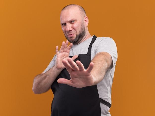 Preek slavische mannelijke kapper van middelbare leeftijd in uniform die handen uitstak naar camera geïsoleerd op oranje muur