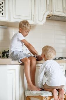 Preeparing jongens bakken zelfgemaakte taart in de keuken. twee broers cooki