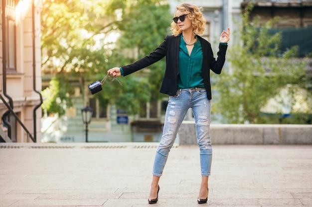 Preety stijlvolle vrouw lopen in de straat in spijkerbroek jas en groene blouse, mode accessoires, elegante stijl, modetrends van de lente dragen