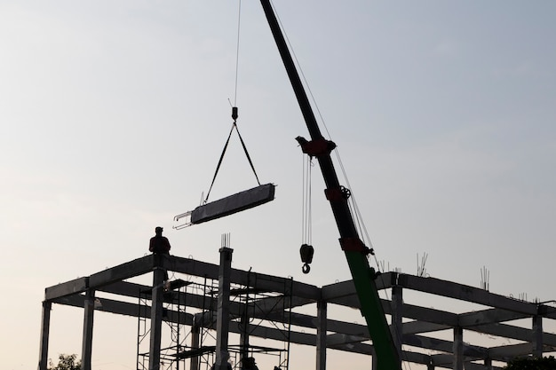 Prefab betonnen balk geïnstalleerd op bouwplaats door mobiele kraan; civieltechnische achtergrond