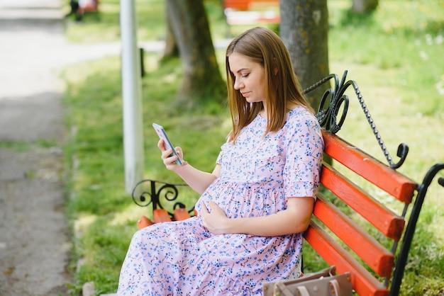 Pregnat vrouw zit op bankje in het park en met behulp van telefoon