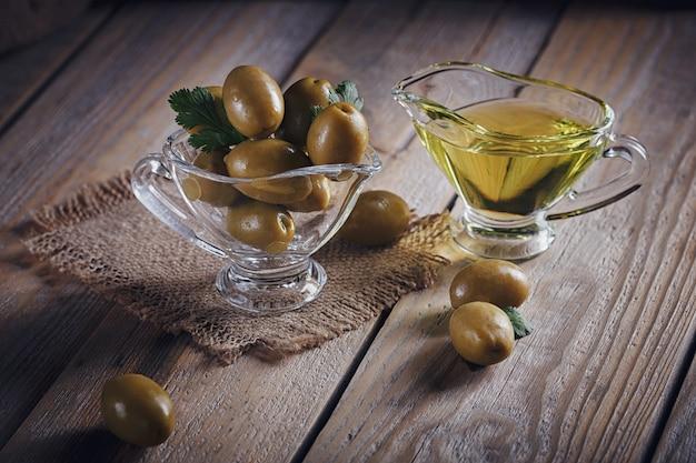 Premium extra vergine olijfolie en groene olijven met verse kruiden op rustieke houten achtergrond.
