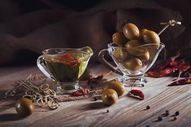 Premium extra vergine olijfolie en groene olijven met verse kruiden, zwarte peper en chili peper op rustieke houten achtergrond.