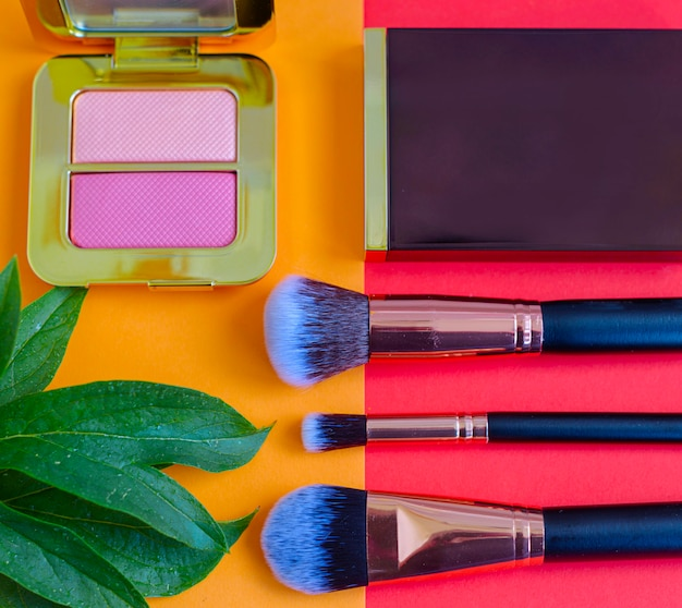 Premium make-upborstels en blush op een gekleurde rode en oranje achtergrond, creatieve cosmetica plat leggen, kopie ruimte