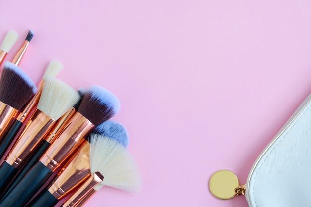 Premium make-upborstels en witte cosmetische tas op roze achtergrond