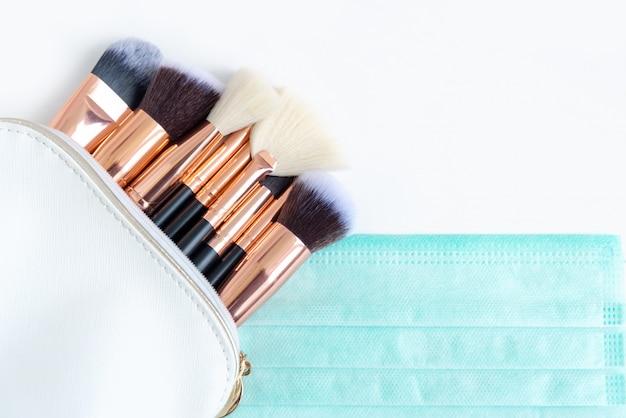 Premium make-upborstels in witte cosmetische zak en beschermend gezichtsmasker op witte achtergrond