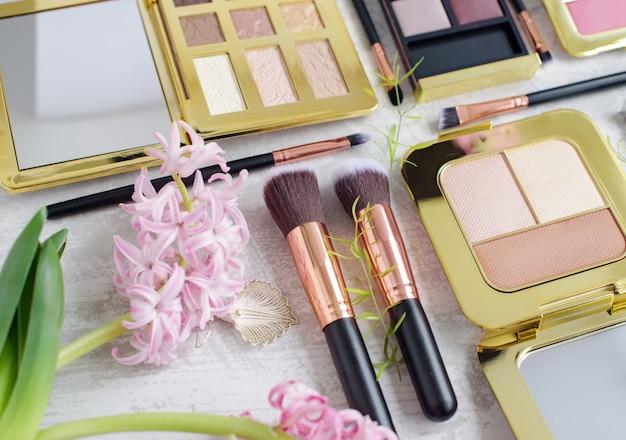 Premium make-upborstels, palet oogschaduw make-up en blush pads op een marmeren achtergrond, creatieve cosmetica plat