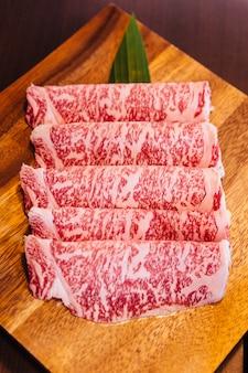 Premium rare slices wagyu a5-rundsvlees met een hoge marmerstructuur op vierkante houten plaat.