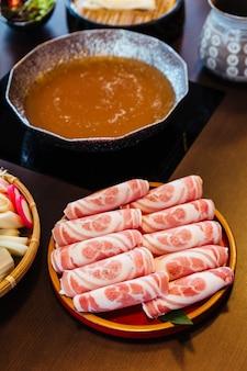 Premium zeldzame plakjes kurobuta (zwart varken) varkensvlees met hooggemarmerde textuur op cirkel houten plaat.