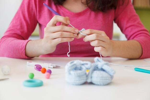 Prenatale moeder die wollen sokjes maakt voor haar baby