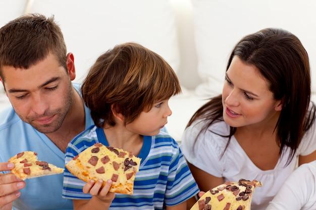 Prenten en zoon die pizza eten in de woonkamer